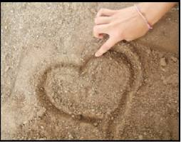 finger tracing heart in the sand