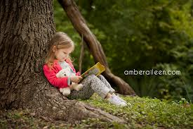 reading little girl by tree